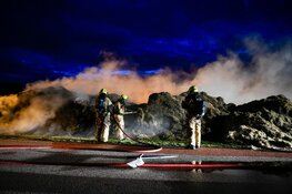 Grasstapel in brand. Grote rookwolk boven wijk De Waal